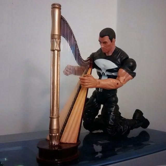Kneeling while trying out the harp.
